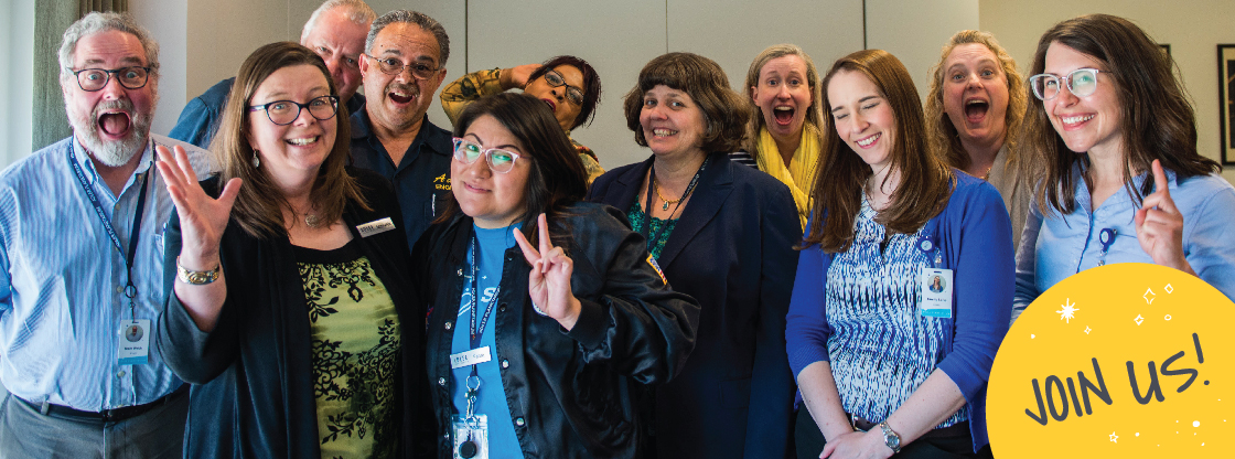 A group of Adler employees smiling happily at the camera while making the peace sign.