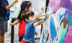 """Two youngsters painting a mural during one of the Adler's """"Moonshot Murals"""" painting events."""