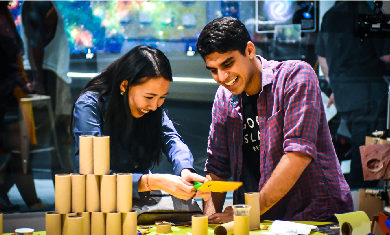 Two Adler guests smile while working together on a Community Design Lab project.