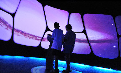 Two children interacting with the A Universe: A Walk Through Space and Time exhibit.