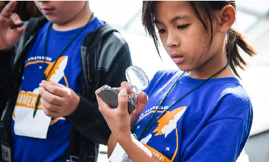 An Adler summer camper peers at a space rock via a magnifying glass.