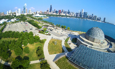 An aerial view of the Adler Planetarium with Chicago's skyline featured in the background.