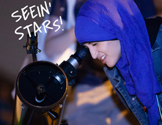 A young woman peers into a telescope an Adler event.