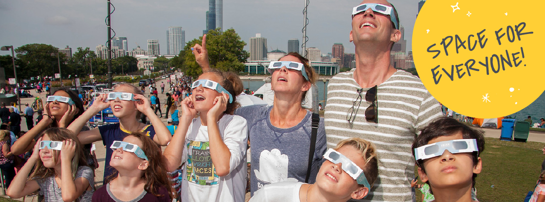 A family looking up at the sky during the 2017 eclipse while wearing their Adler eclipse-viewing glasses.