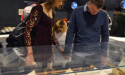 """A young couple peers down at a small display of historic astronomy artifacts in the Adler's """"Astronomy in Culture"""" exhibit."""