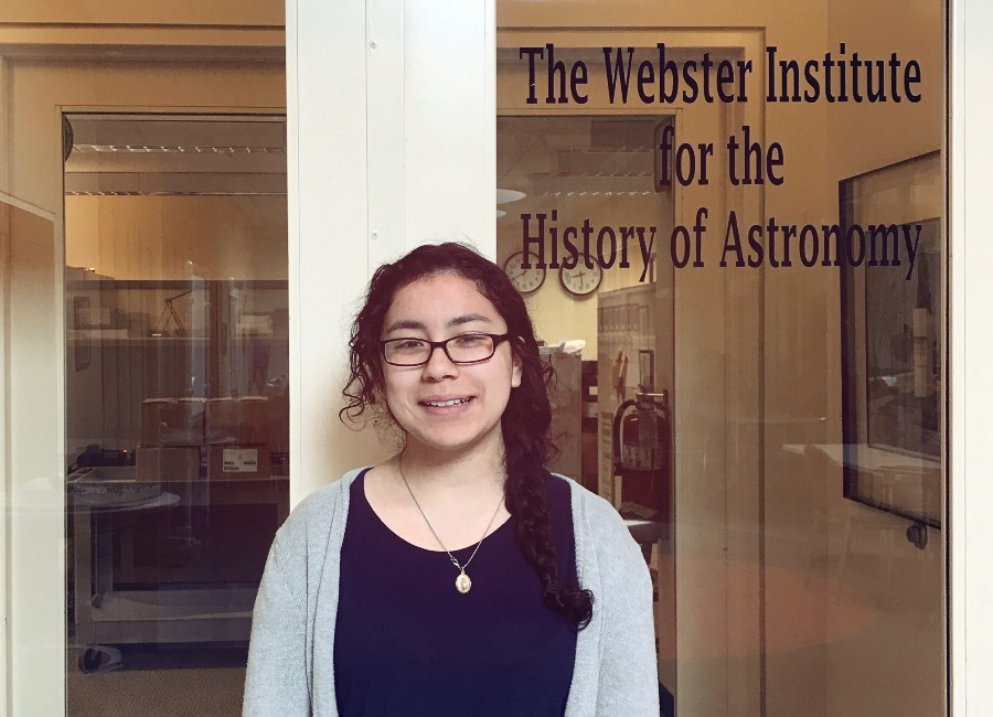 Headshot of Brenda, Adler Teen Collections Intern, standing in front of the History of Astronomy collections door