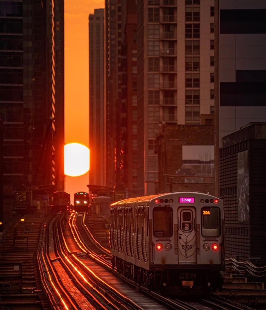 The Sun sets during a Chicagohenge as a CTA train travels towards it.