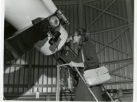 A person looking through the Doane Observatory telescope at the Adler Planetarium