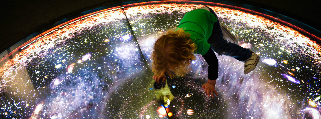 A child interacting with a lit-up cosmic floor display.