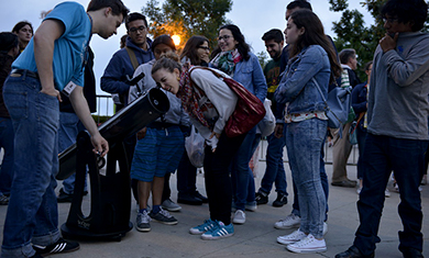 A teen peers into a telescope at an Adler event.