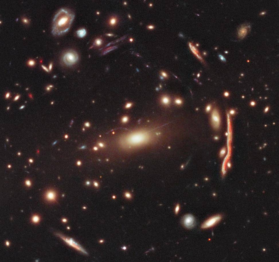 This image depicts a cluster of distorted galaxies. The distorted shapes in the cluster shown here are distant galaxies, from which the light is bent by the gravitational pull of dark matter within the cluster of galaxies.