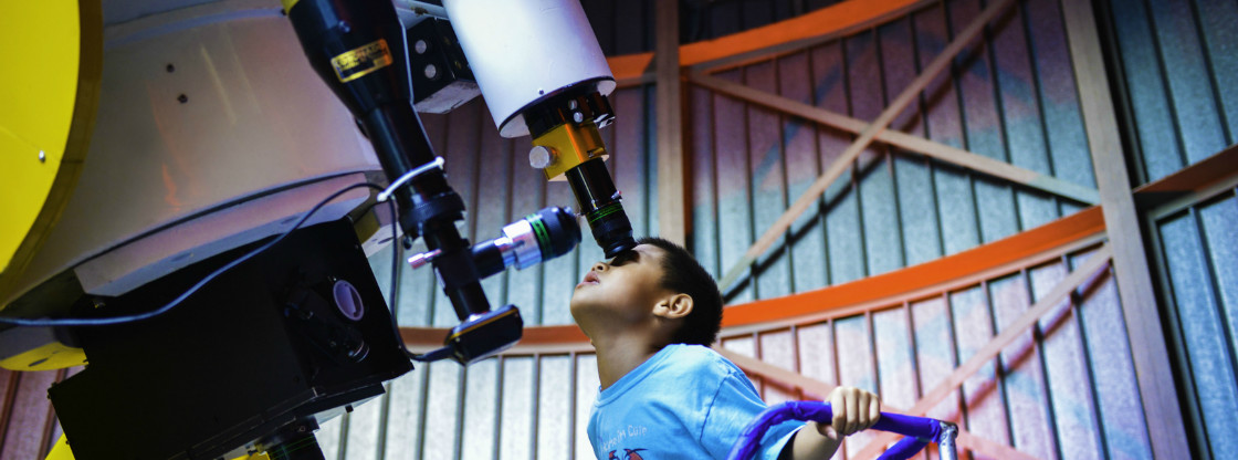 A young boy peers into a telescope in the Adler's Doane Observatory.