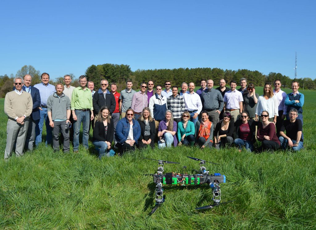 Dragonfly team in standing in two rows in a green field. in the foreground is the Dragonfly drone.