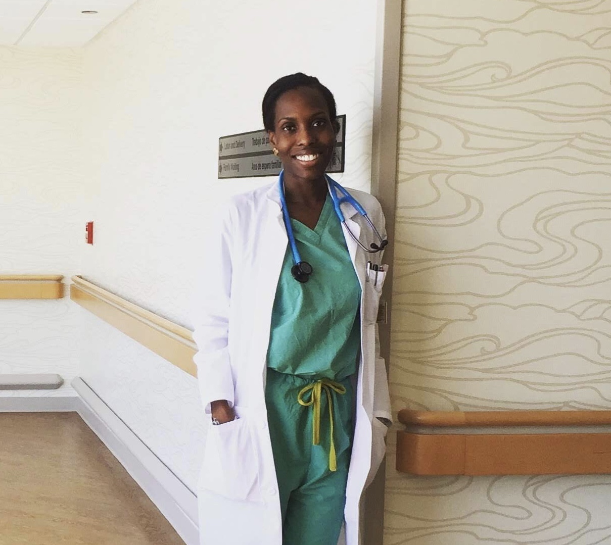 A smiling Choumika poses in her hospital scrubs.