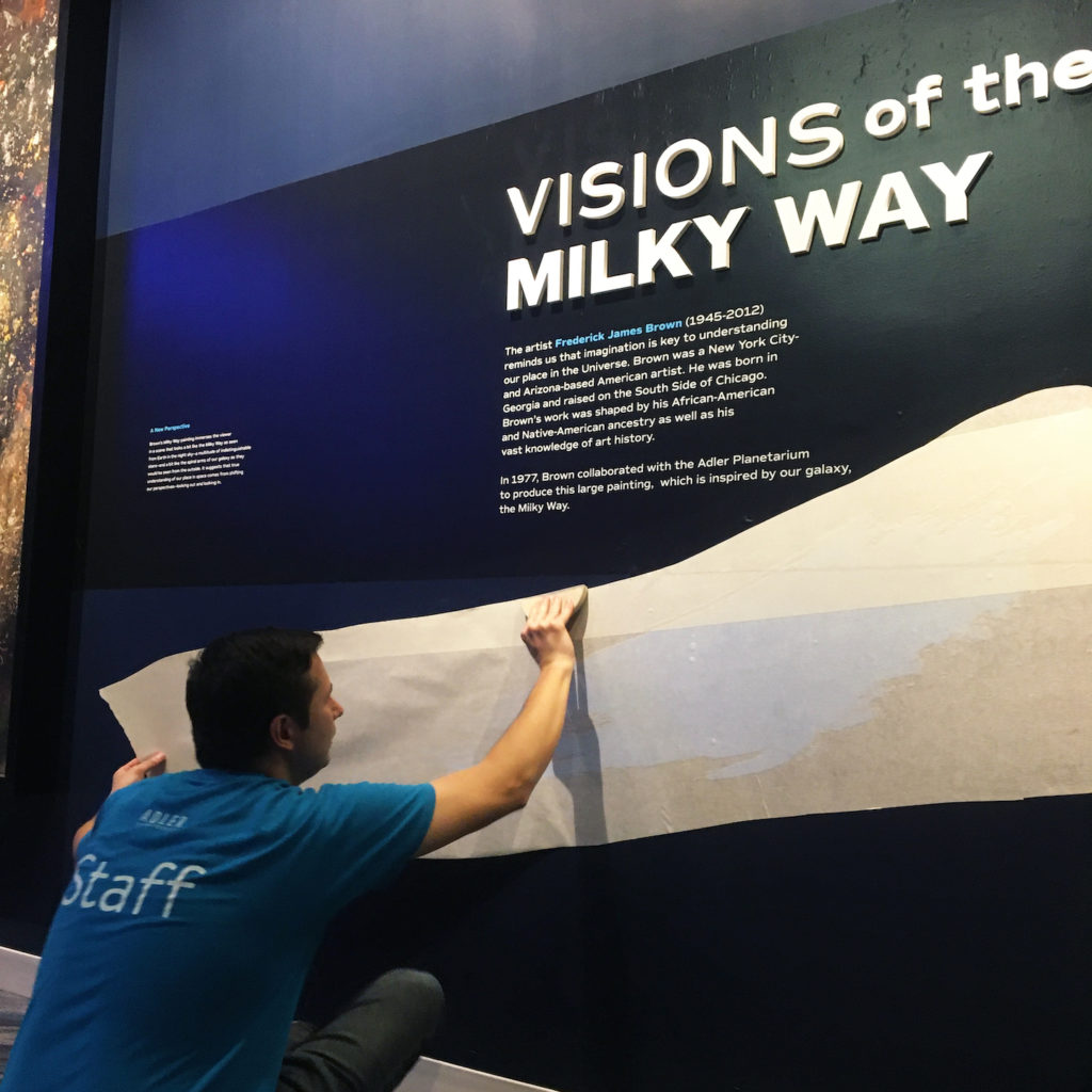 "Neil Adam installing a graphic in Chicago's Night Sky on a wall featuring Frederick J. Brown's painting, ""Milky Way."""