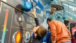 """A young boy reaches for a model of Earth in the Adler's """"Solar System"""" exhibit."""