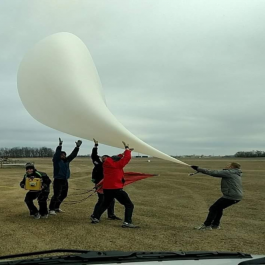 A group of teens pictures testing out a high-altitude balloon for flight in a field.