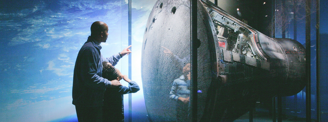 "A father and son gazing at the Gemini 12 spacecraft, located in the Adler's ""Mission Moon"" exhibition."