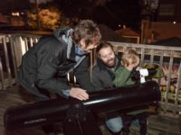 Adler telescope volunteer helps man and his child find stars and planets in the night sky through a telescope.