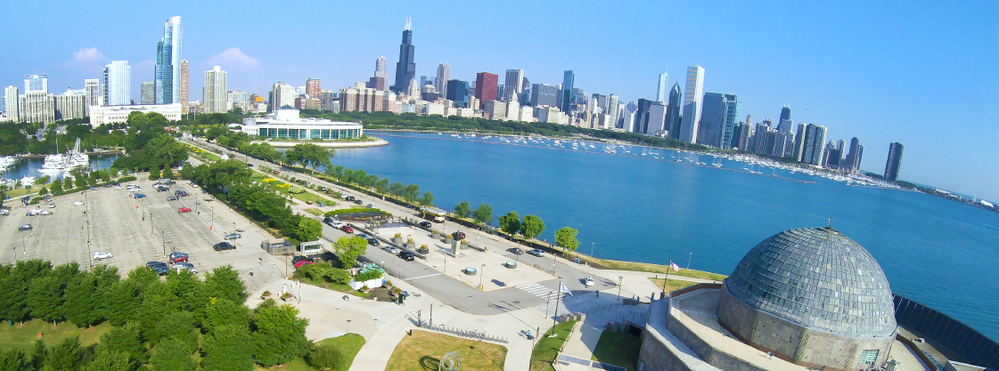 Aerial view of the Adler Planetarium with the Chicago skyline in the background.