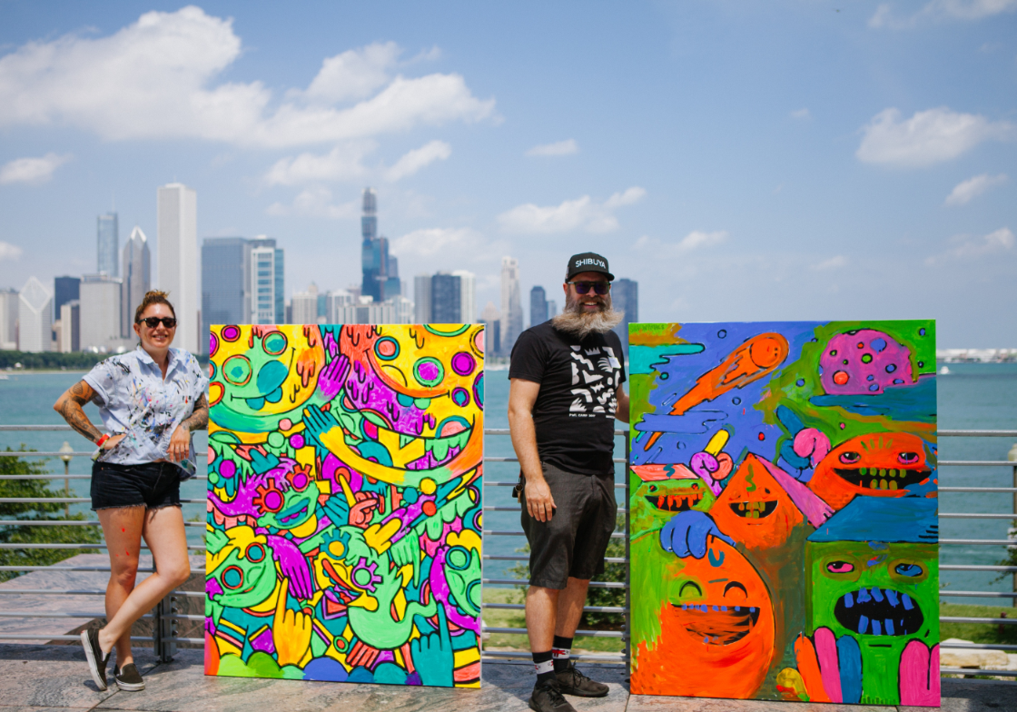 Lauren Asta (left) and Shawn Smith (right) pose with their completed Moonshot Murals painted by Adler guests during Moon Bash on July 20, 2019.