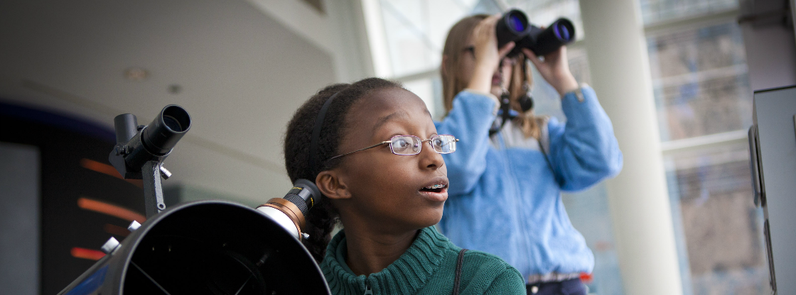 Two young girls peering out through a telescope and binoculars at the Adler Planetarium.