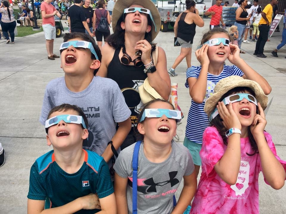 Photo of family looking up safely at the Sun during Adler's Eclipse Fest in August 2017.