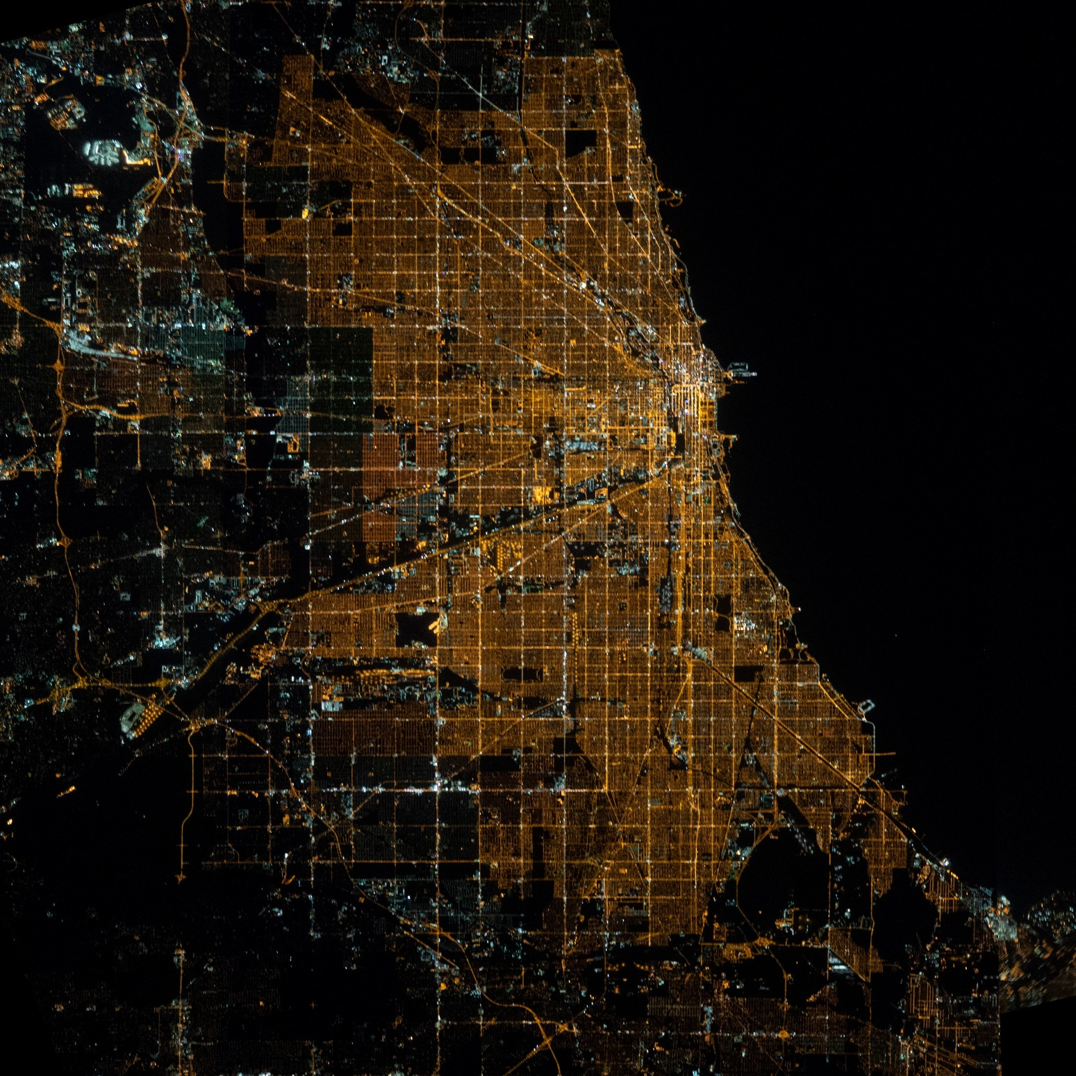A bird's eye view of Chicago at night, with the city's gridline highly visible.