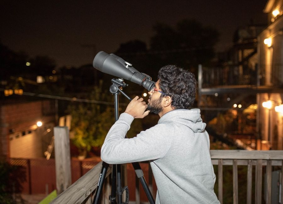 Man looking through a pair of telescopes into Chicago's night sky.