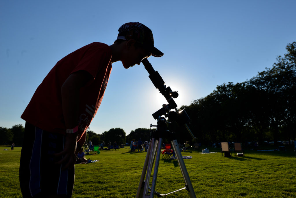 Looking through a telescope at a park.