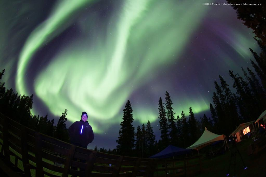 Michelle Nichols standing in front of the Northern Lights at Wood Buffalo National Park, 2015. Photo Credit: Yuichi Takasaka