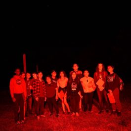 A picture taken of a group of YOLO participants at a night time activity outside.