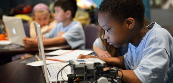 Summer Camp Attendee Playing With Robotics on Computers