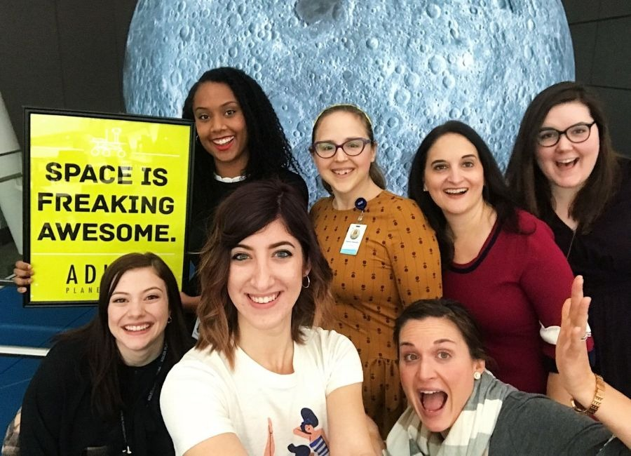 A group of Adler staff smile while posing in front of an inflatable Moon exhibition.