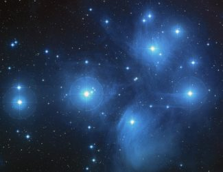 This is an image of the Pleiades star cluster. You can see in this image faint clouds of bluish nebulae and dozens of bright stars scattered in the distance.