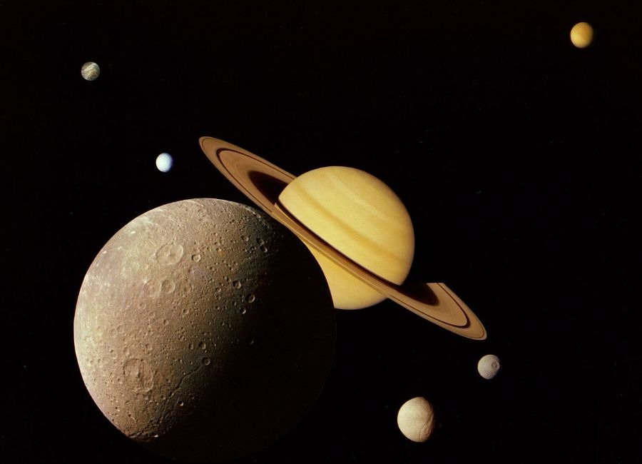 This montage of images of the Saturnian system was prepared from an assemblage of images taken by the Voyager 1 spacecraft during its Saturn encounter in November 1980. This artist's view shows Dione in the forefront, Saturn rising behind, Tethys and Mimas fading in the distance to the right, Enceladus and Rhea off Saturn's rings to the left, and Titan in its distant orbit at the top. The Voyager Project is managed for NASA by the Jet Propulsion Laboratory, Pasadena, California. Credit: NASA/JPL
