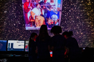 4 Adler Summer Camp campers learn about space visualizations in the Grainger Sky Theater.