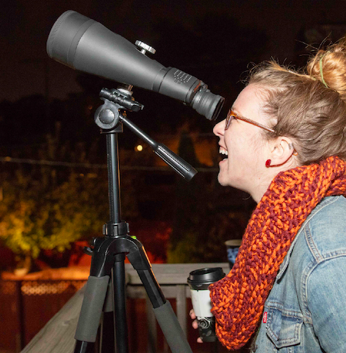 An attendee looking through a telescope during a 'Scopes In The City neighborhood event with the Adler Planetarium.
