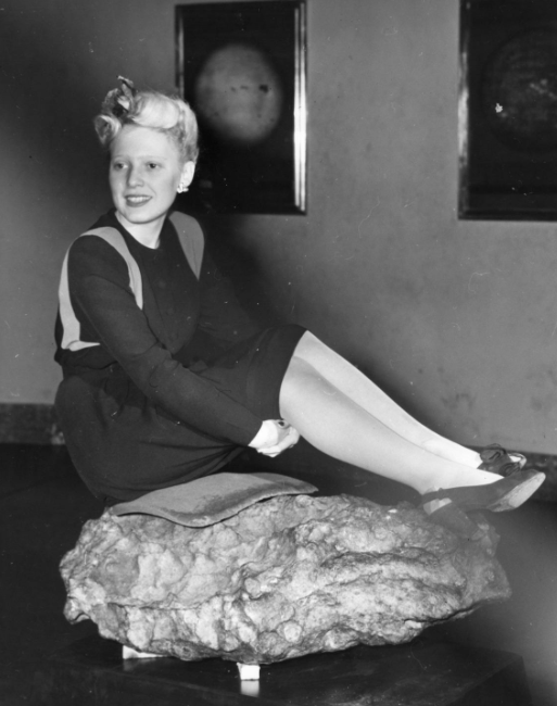 A woman sitting on a meteorite at the Adler Planetarium