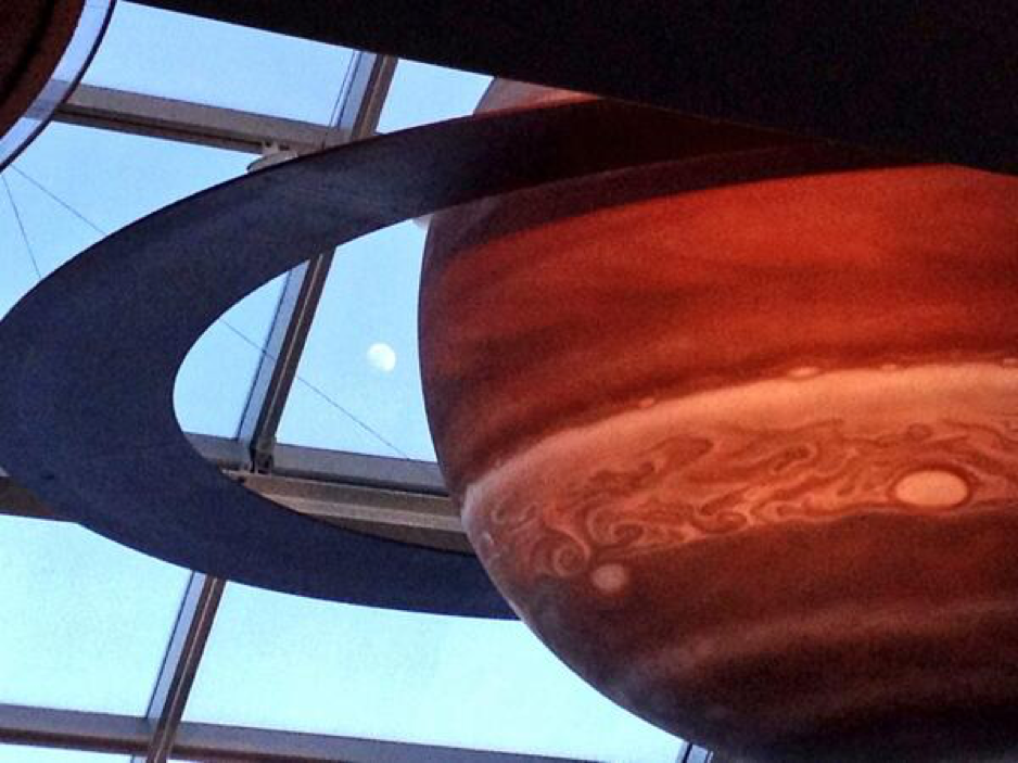 A photo of the Moon peaking through the window panels inside the Adler Planetarium's Solar System Gallery.
