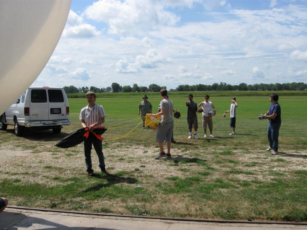 Spencer Gore (left foreground, black and white stripped shirt) and Far Horizon teens in 2011 prepare a balloon for a payload launch.