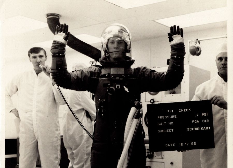Robert Davidson, shown on the left of the image holding a microphone, seen here conducting a space suit fit check with Astonaut Rusty Schweikart on December 17, 1966.