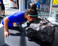 "A summer camper looking at a space rock in the Adler's ""Solar System"" gallery."