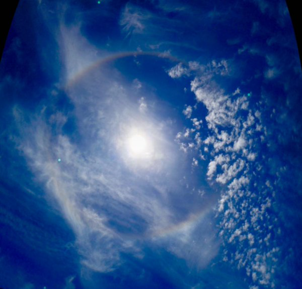 Ice crystals in the atmosphere bending light around the Sun to form a rainbow.