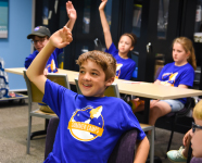 Adler teen summer campers smiling and raising their hands while in a classroom setting.