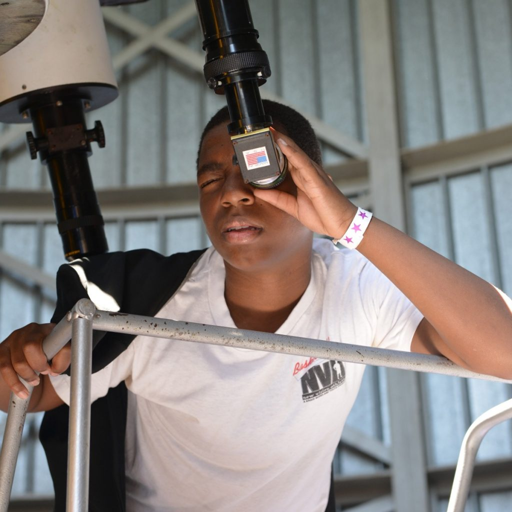 Teen looking through Doane Observatory telescope