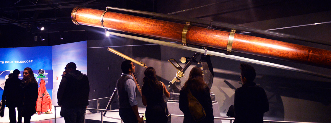 """Guests viewing a large telescope in the Adler's """"Telescopes..."""" exhibition."""