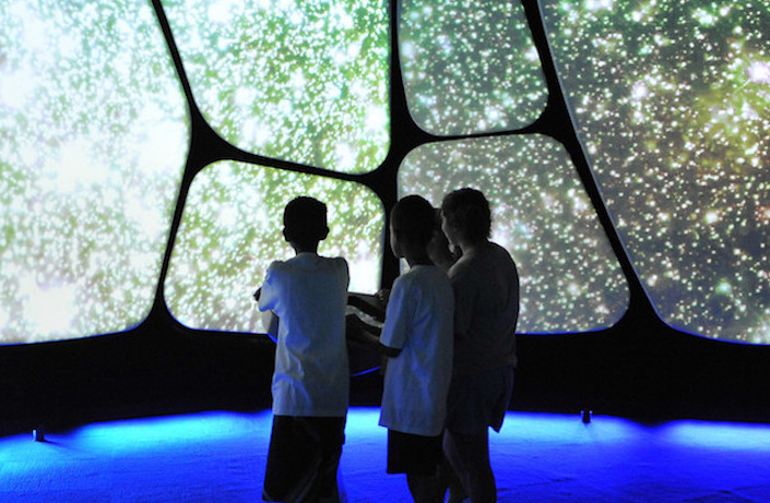 The silhouettes of three children as they view a large visual presentation in the Adler's The Universe: A Walk Through Space and Time exhibition.