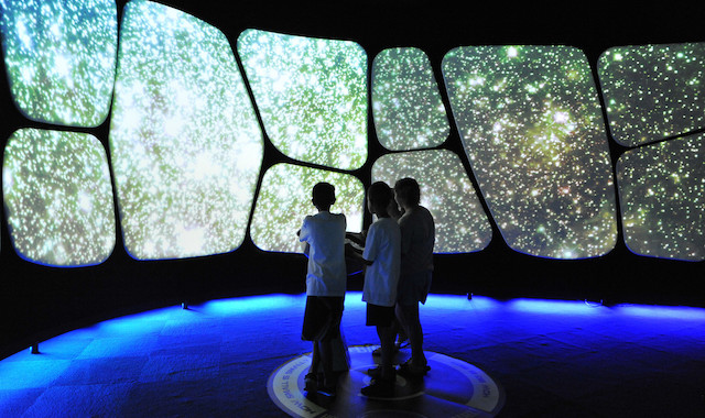 A trio of children playing with an interactive video display of the cosmos.