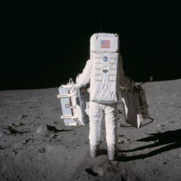 Buzz Aldrin deploying Apollo 11 instruments on the Moon, his back facing the camera.